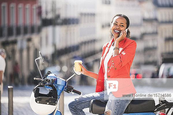 Lachende junge Frau mit Motorroller telefoniert in der Stadt  Lissabon  Portugal