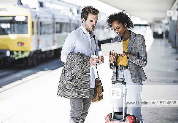 Junger Geschäftsmann und Geschäftsfrau benutzen gemeinsam Tabletten am Bahnhof
