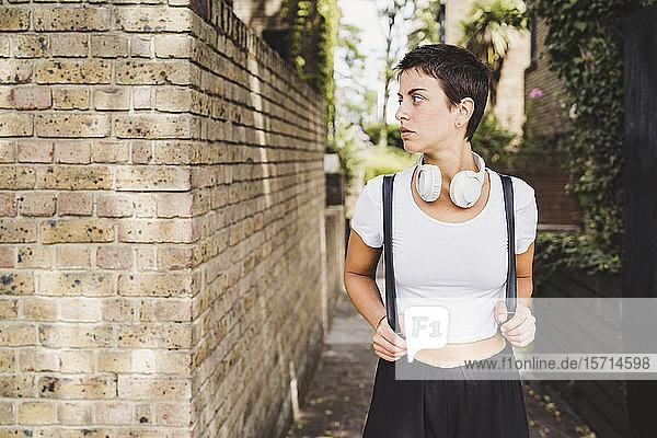 Porträt einer Frau mit Kopfhörer und Rucksack Porträt einer Frau mit Kopfhörer und Rucksack