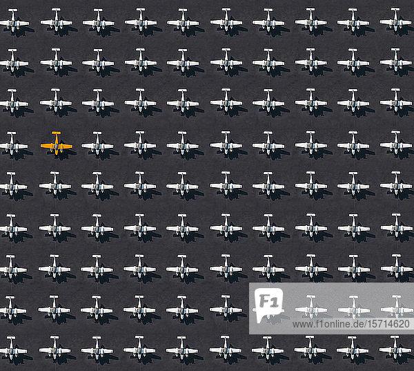 Luftbild eines einzelnen orangefarbenen Flugzeugs  umgeben von ausschließlich weißen Flugzeugen
