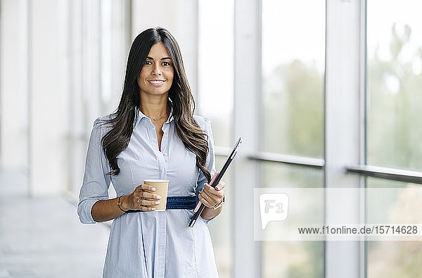 Portrait of smiling businesswoman with tablet and takeaway coffee at the window
