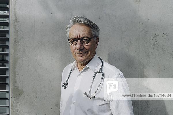 Porträt eines selbstbewussten Oberarztes an einer Betonwand