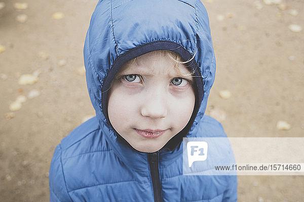Portrait of grumpy little boy wearing blue anorak
