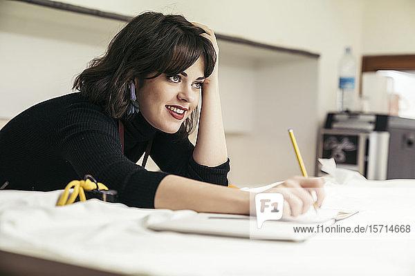 Porträt einer jungen Modedesignerin am Schreibtisch lehnend
