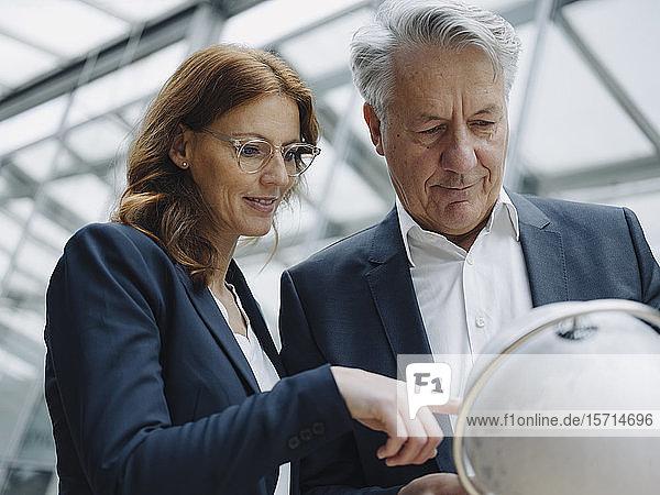 Geschäftsmann und Geschäftsfrau betrachten den Globus im Amt