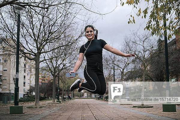 Porträt einer jungen Frau in schwarzer Sportkleidung  die in die Luft springt  während sie mit Kopfhörern Musik hört