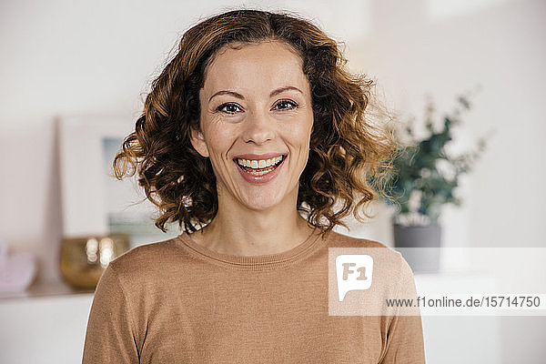 Portrait of happy brunette woman at home