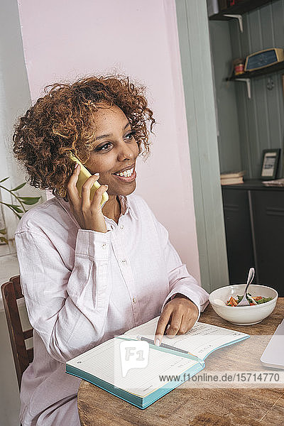 Young woman working at home talking on the phone