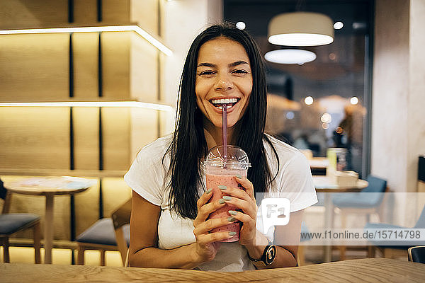 Black-haired woman drinking a smoothie in cafe