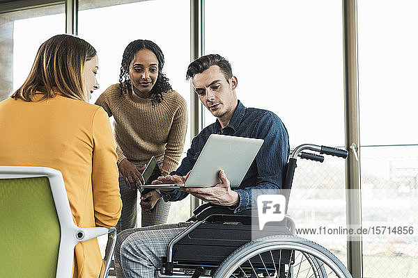 Young businessman in wheelchair showing laptop to colleague in office
