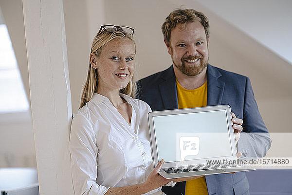 Porträt eines selbstbewussten Geschäftsmannes und einer selbstbewussten Geschäftsfrau im Büro bei der Präsentation eines Laptops