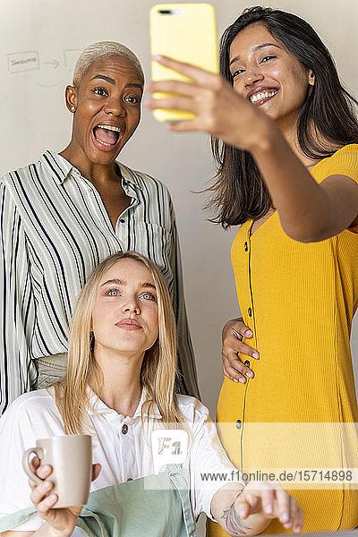 Glückliche Geschäftsfrauen  die ein Selfie im Amt haben
