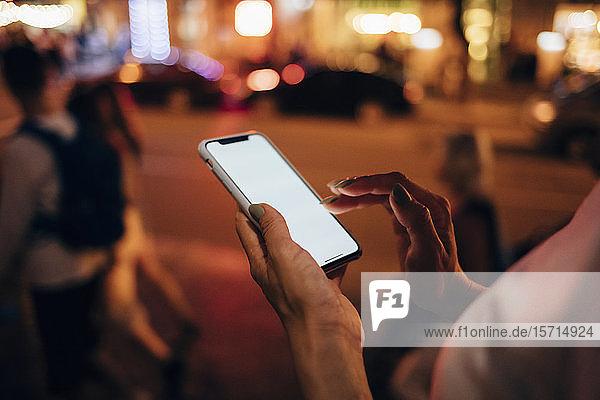Hände einer Frau  die nachts ihr Smartphone in der Hand hält  Nahaufnahme