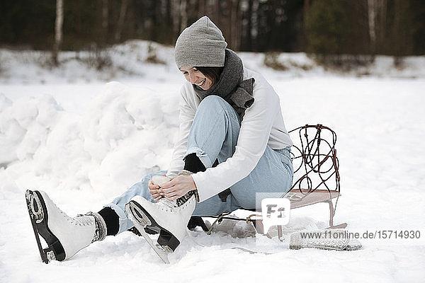 Lächelnde Frau zieht Schlittschuhe auf Schneefeld an