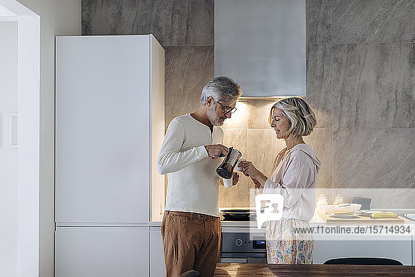 Mature couple in kitchen at home in the morning