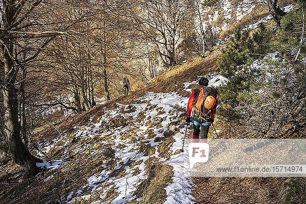 Zwei Wanderer wandern durch verschneiten Wald  Orobie-Alpen  Lecco  Italien