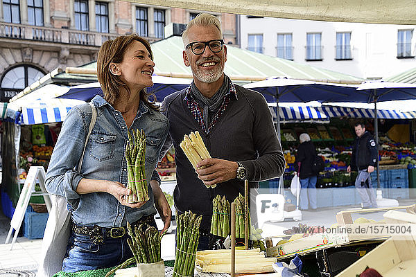 Happy mature couple choosing asparagus at a market stall