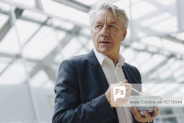 Porträt eines hochrangigen Geschäftsmannes  der im Amt Müsli isst
