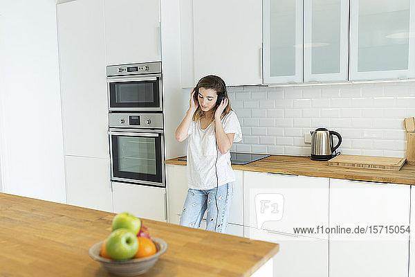 Weibliche Teeangerin mit Kopfhörern in der Küche