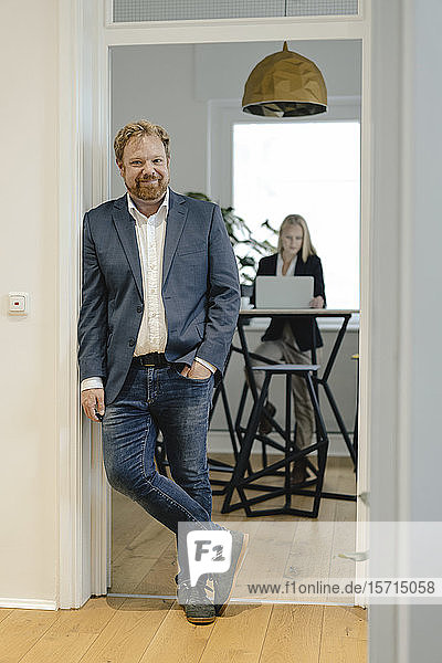 Portrait of casual businessman in office with businesswoman in background