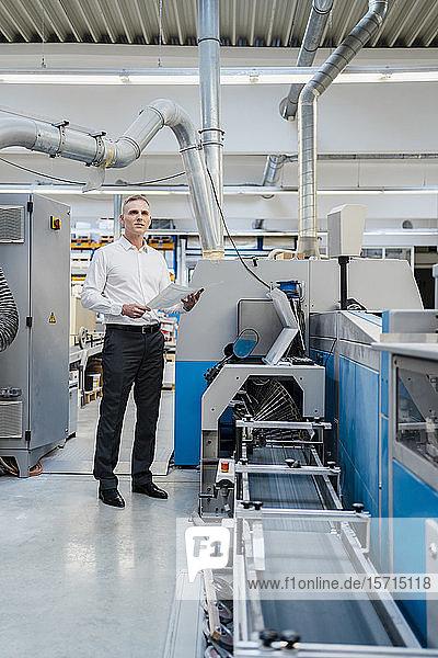 Geschäftsmann hält Papier in einer Fabrik
