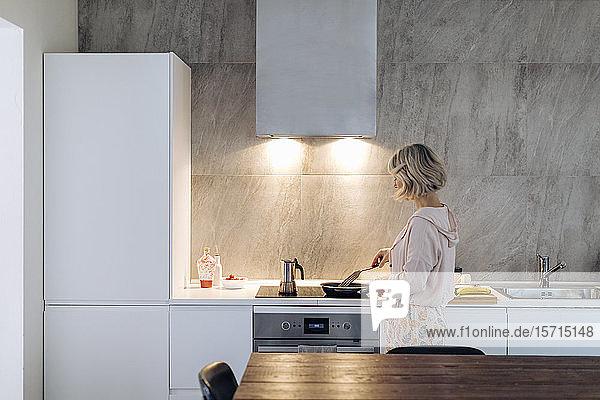 Reife Frau kocht zu Hause in der Küche Reife Frau kocht zu Hause in der Küche