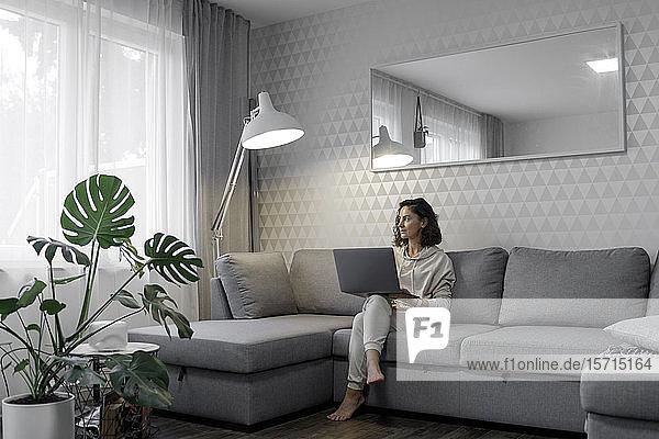 Frau mit Laptop  die zu Hause auf der Couch sitzt und aus dem Fenster schaut