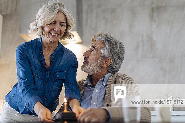 Älteres Paar feiert Geburtstag mit Kuchen in der heimischen Küche Älteres Paar feiert Geburtstag mit Kuchen in der heimischen Küche