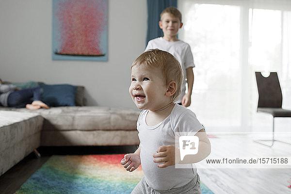 Porträt eines glücklichen kleinen Jungen im heimischen Wohnzimmer mit seinem kleinen Bruder im Hintergrund