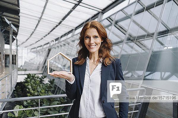 Porträt einer selbstbewussten Geschäftsfrau  die ein Hausmodell im Amt hält
