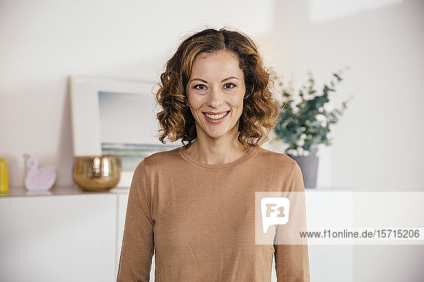 Portrait of smiling brunette woman at home