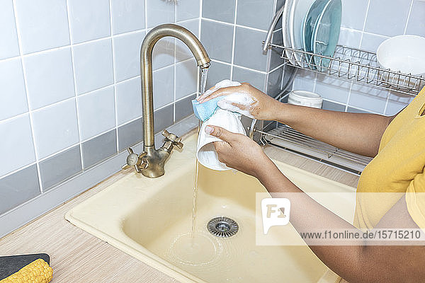 Close-up of woman washing a cup in kitchen