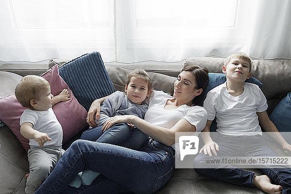 Familie entspannt sich zu Hause auf der Couch im Wohnzimmer