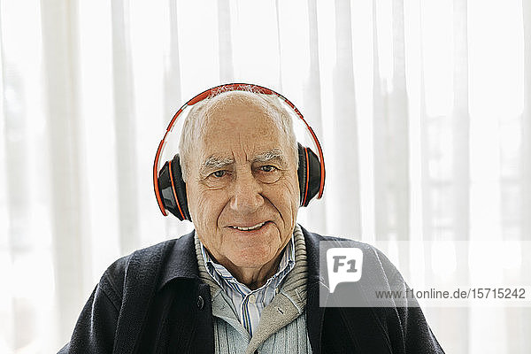 Portrait of smiling senior man listening music with headphones