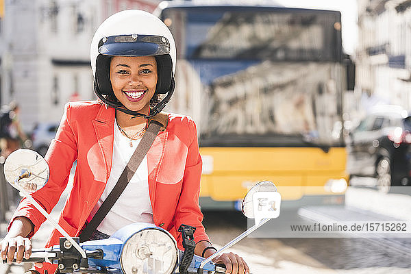 Portrait of happy young woman riding motor scooter in the city  Lisbon  Portugal