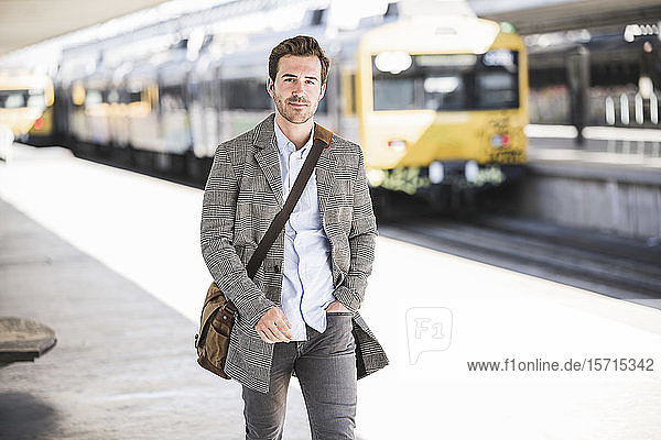 Zuversichtlicher junger Geschäftsmann geht am Bahnhof