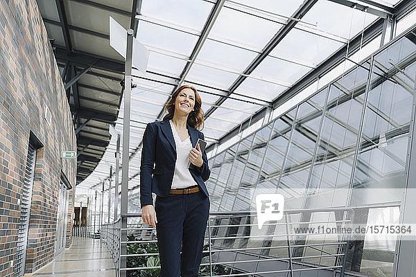 Lächelnde Geschäftsfrau mit einer Tablette in der Hand in einem modernen Bürogebäude
