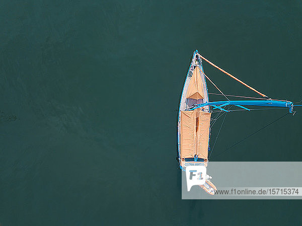 Indonesia  Bali  Serangan  Aerial view of sailboat floating in green sea water