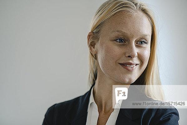 Porträt einer lächelnden blonden jungen Geschäftsfrau