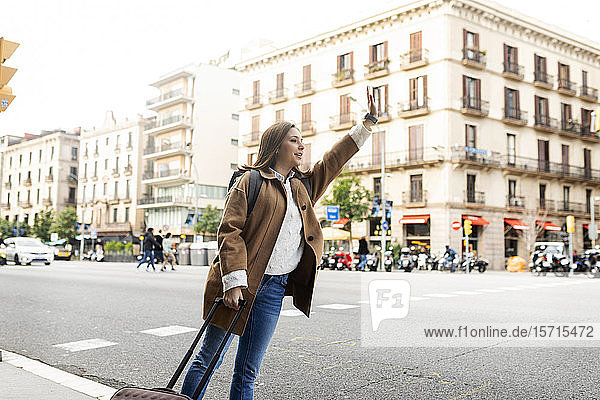 Young woman in the city hailing a taxi  Barcelona  Spain