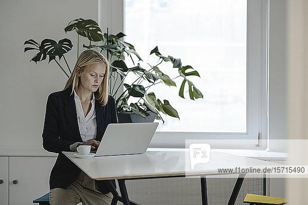 Junge Geschäftsfrau benutzt Laptop im Büro
