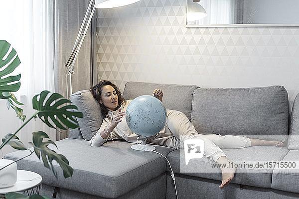 Porträt einer Frau  die zu Hause auf der Couch liegt und auf den Globus schaut