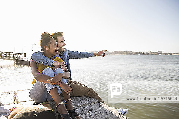 Happy young couple sitting on pier at the waterfrontlooking at view  Lisbon  Portugal