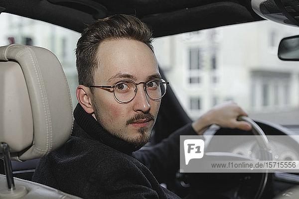Porträt eines jungen Autofahrers mit Brille