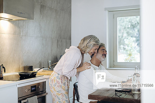 Affectionate mature couple at table in kitchen at home