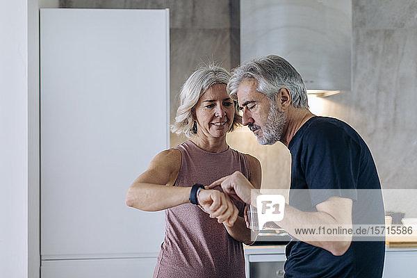 Reifes Paar benutzt Smartwatch in der Küche zu Hause