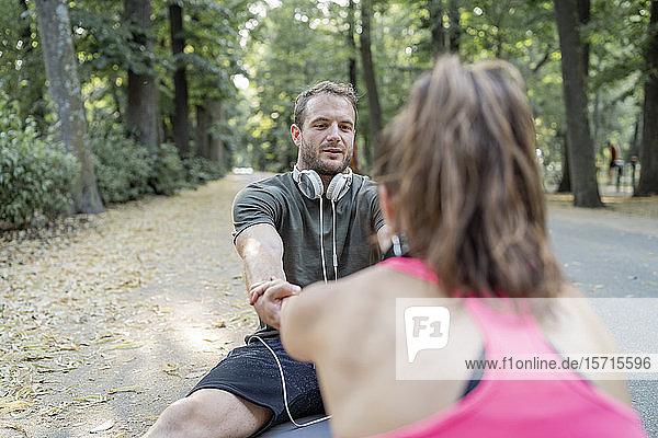 Mann und Frau trainieren auf einem Fitnessparcours