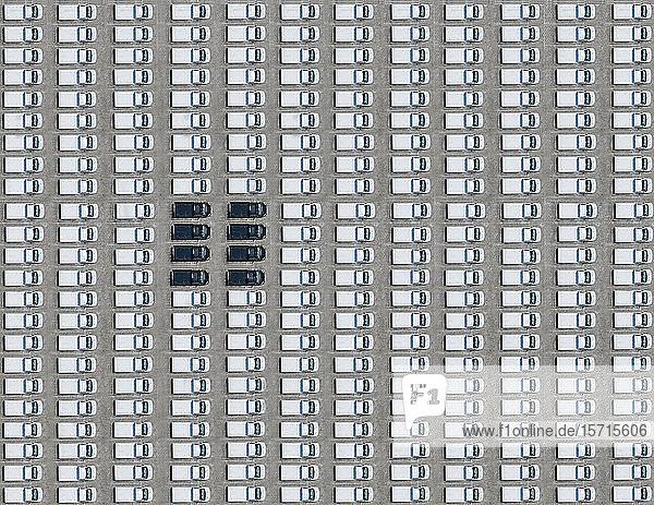 Luftbild von wenigen schwarzen Autos  die zwischen ausschließlich weißen Autos geparkt sind