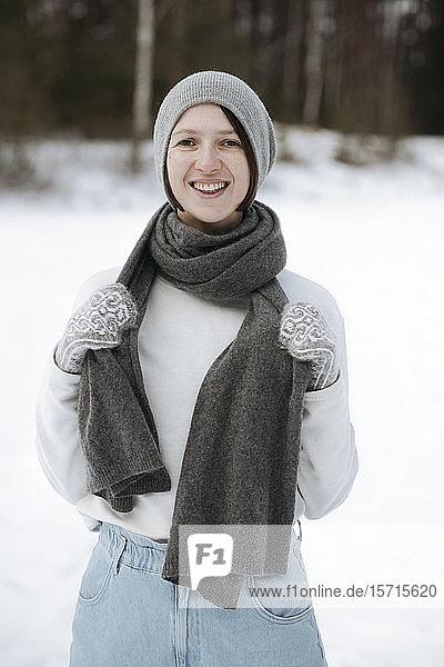 Portrait of happy woman standing on a snow field
