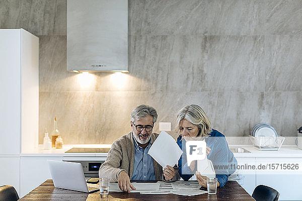 Reifes Paar mit Papieren und Laptop auf dem Küchentisch zu Hause Reifes Paar mit Papieren und Laptop auf dem Küchentisch zu Hause